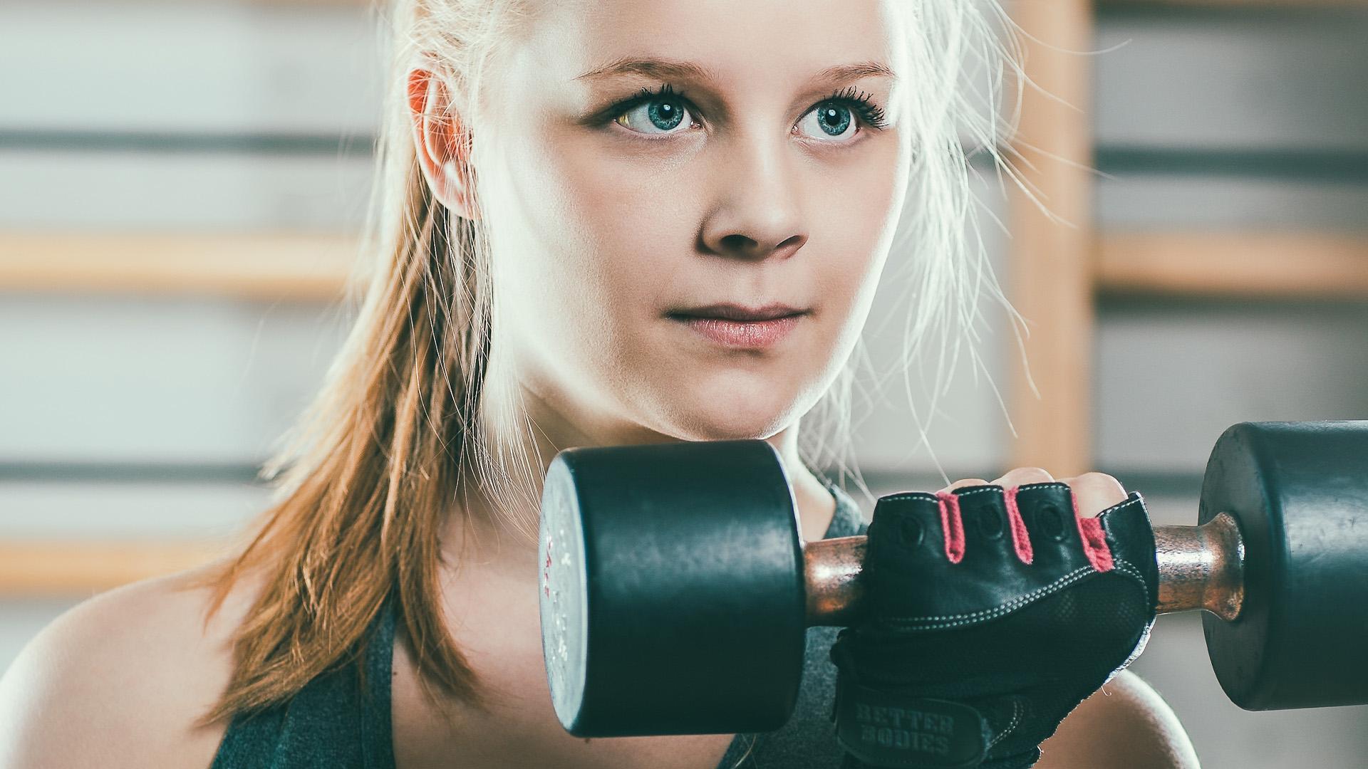 Ung kvinna tränar med hantel.