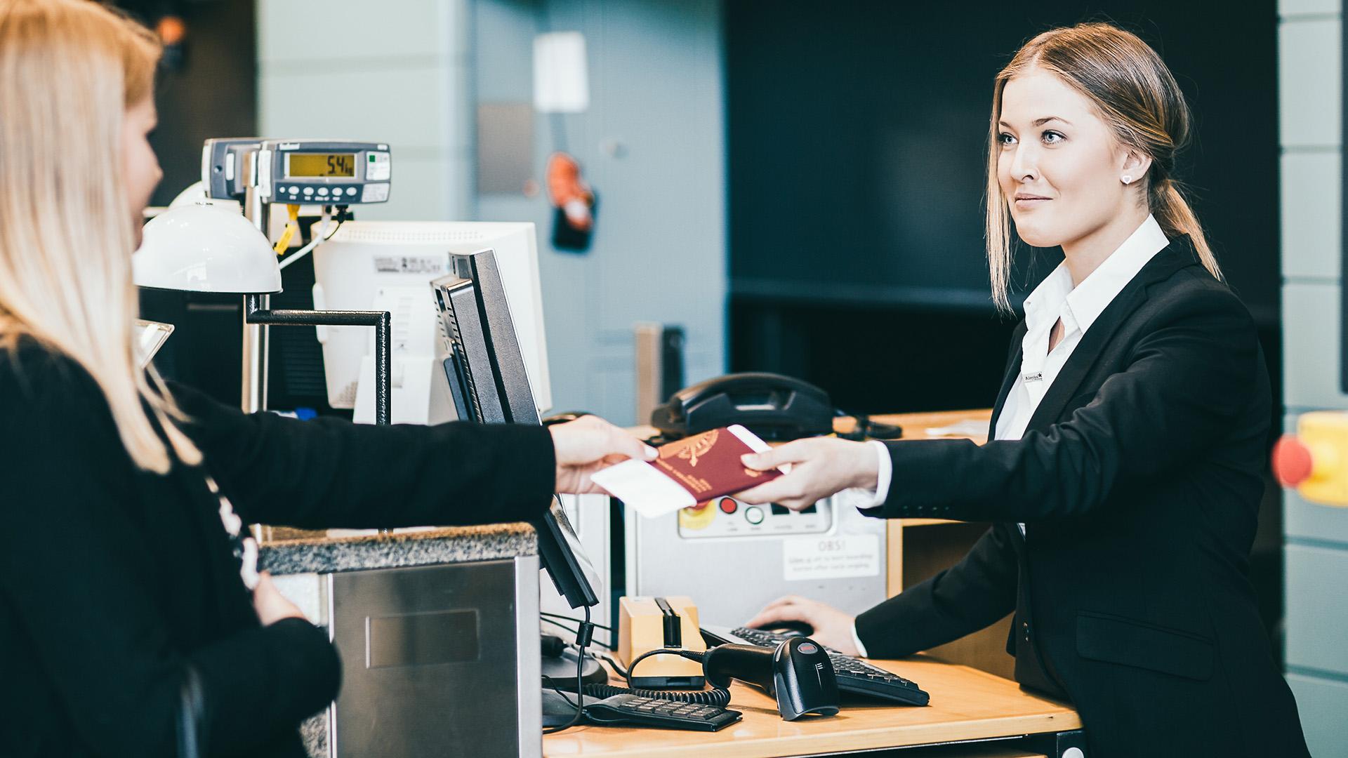Receptionist lämnar ut pass och boardingkort till gäst.