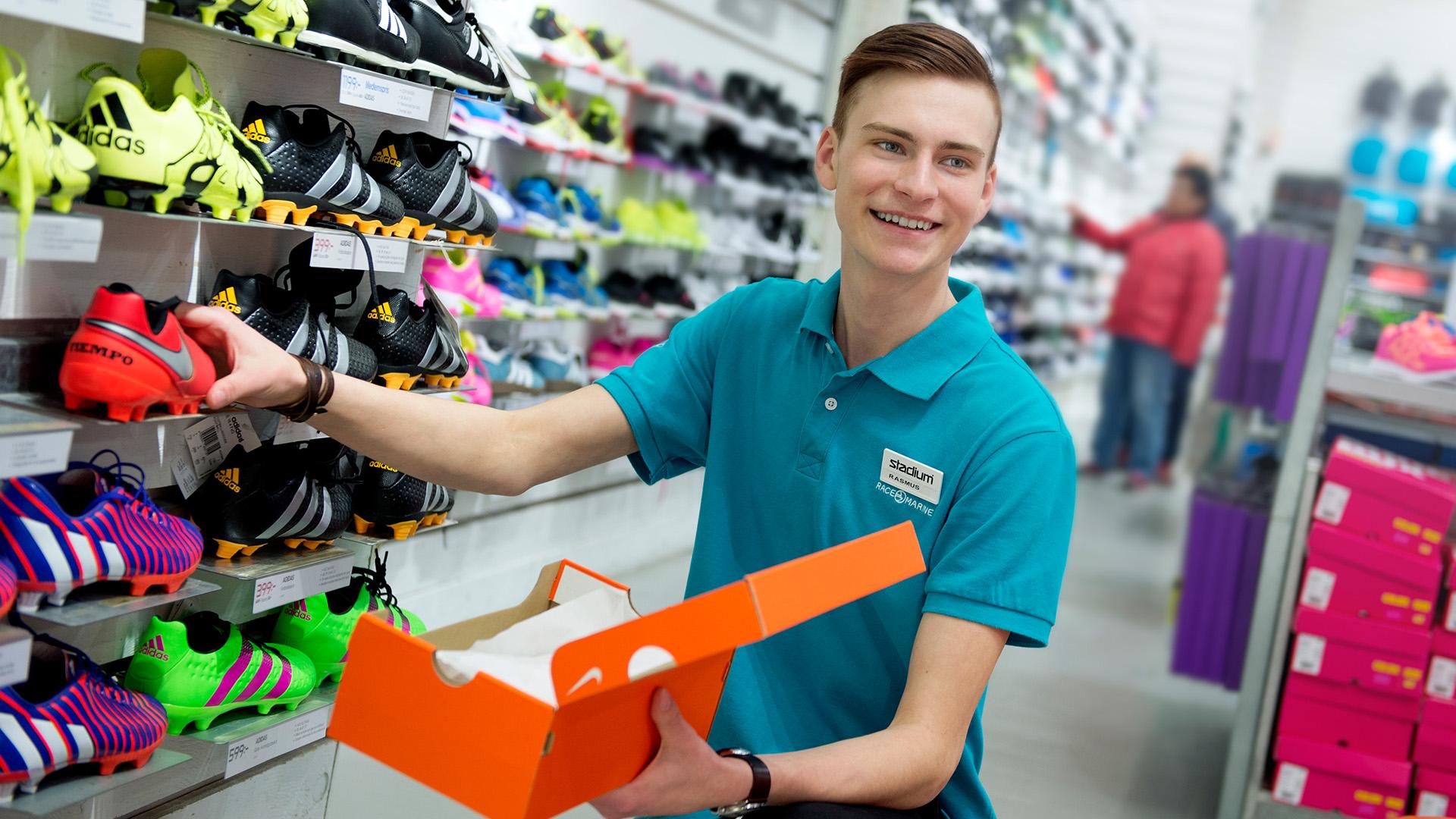 Ung man plockar upp varor i sportbutik.
