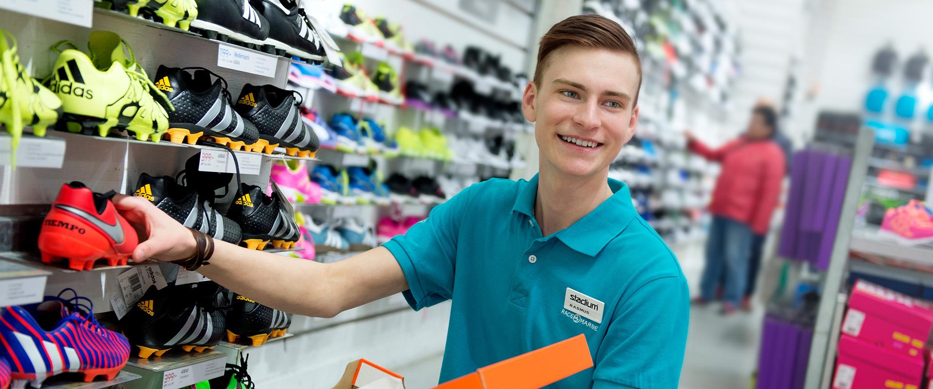 Ung kille plockar upp skor på hylla i sportbutik