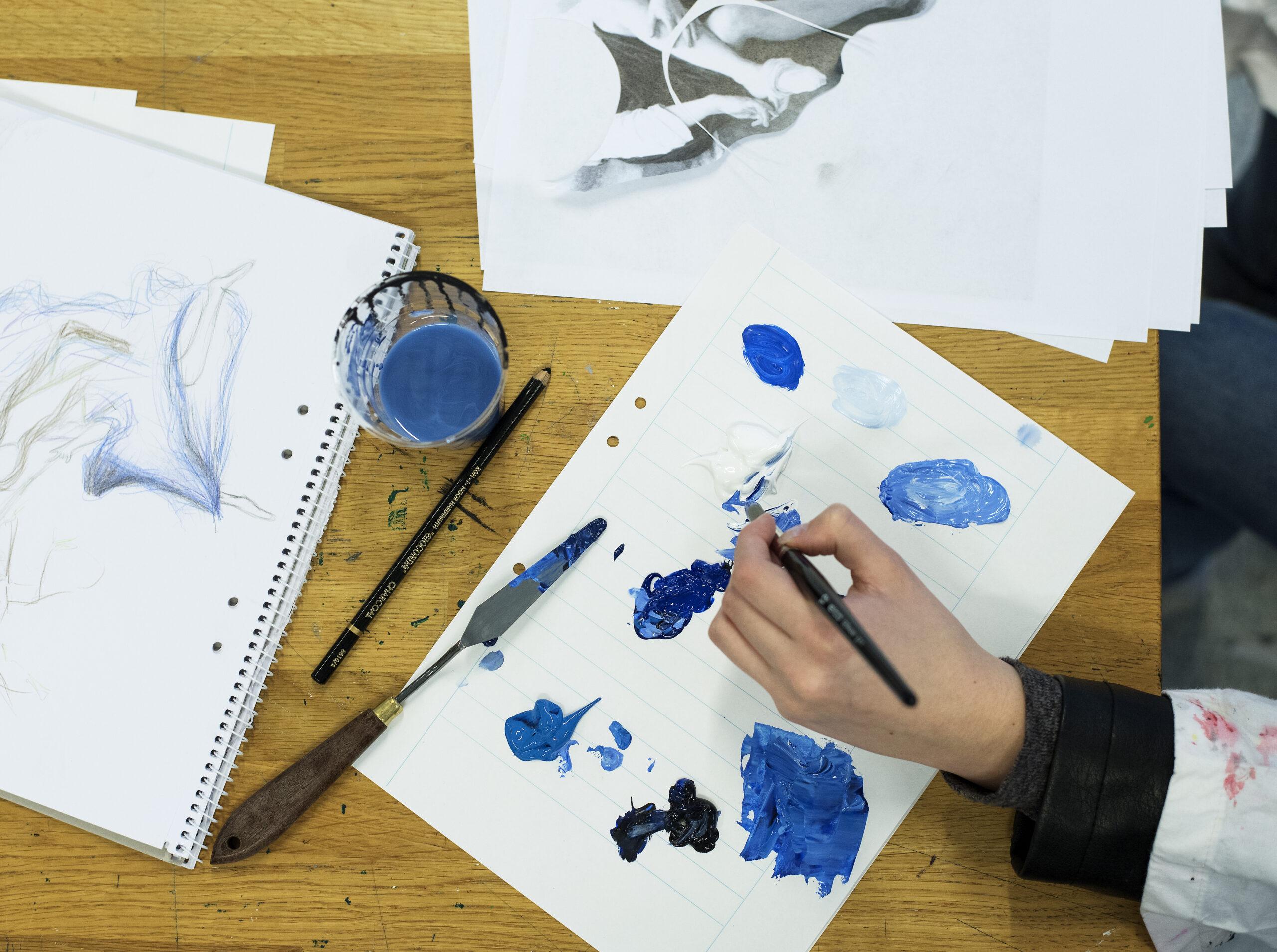 En elev målar med vattenfärg.