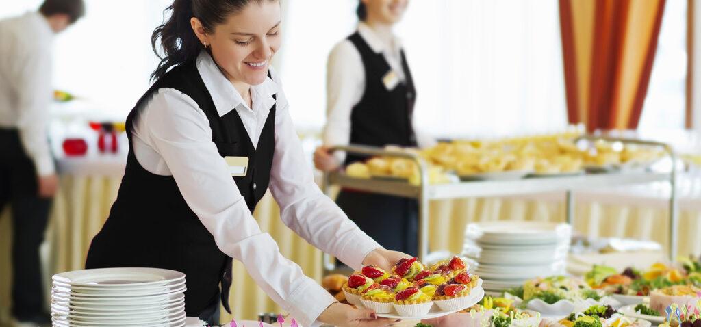 Servitris ställer ner ett fat med mat på ett bord