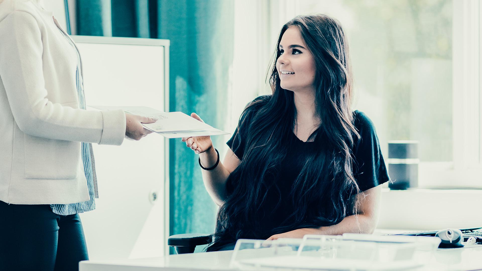 Ung kvinna på kontor tar emot papper av kollega.