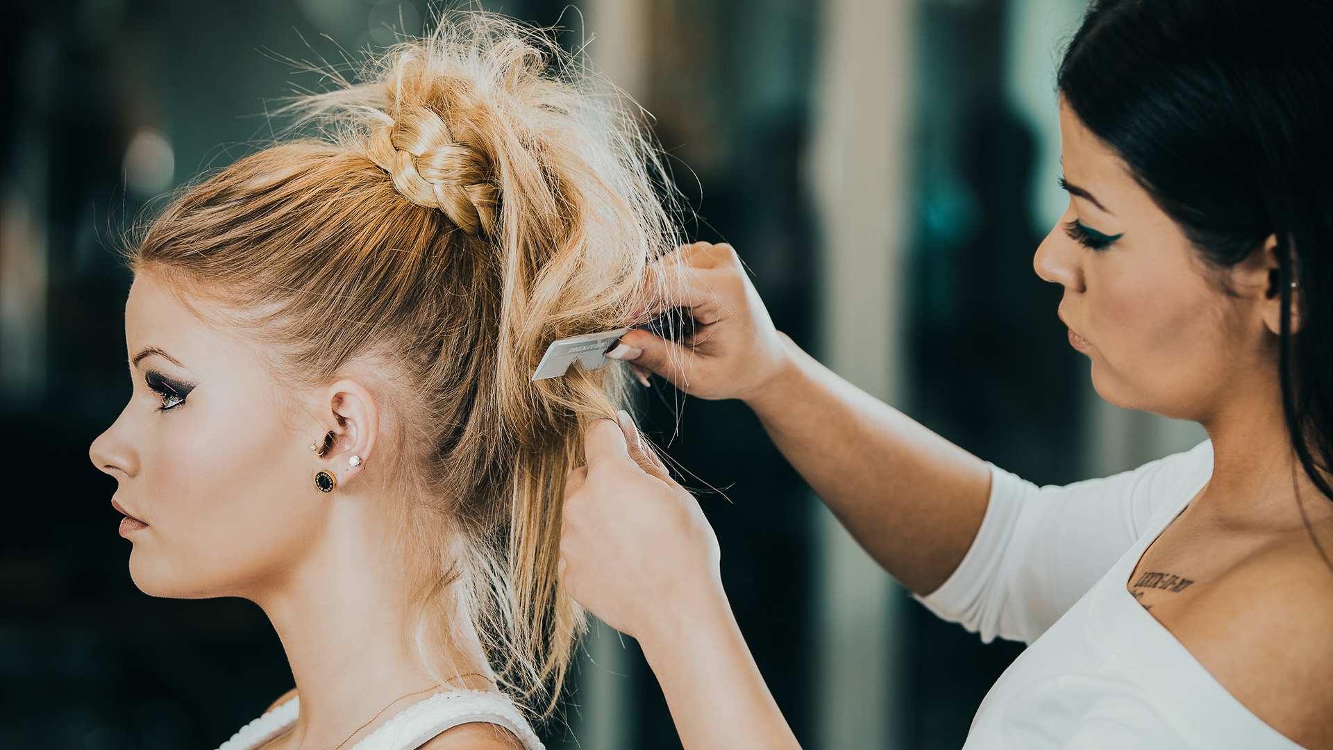 Ung kvinnlig frisör kammar kvinnas hår.
