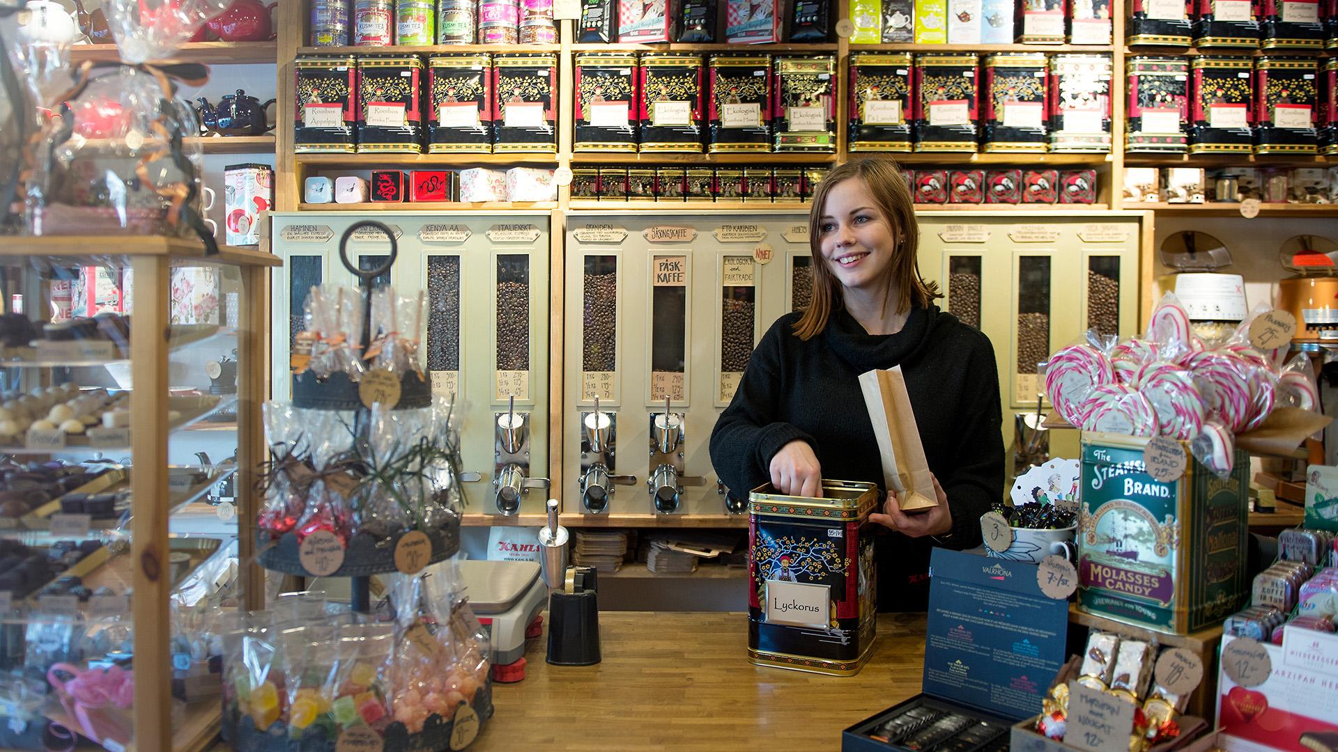Ung kvinna säljer kaffe i specialistbutik.