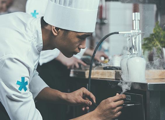 Ung kock skapar rök under ett glas som ska användas vid matservering.