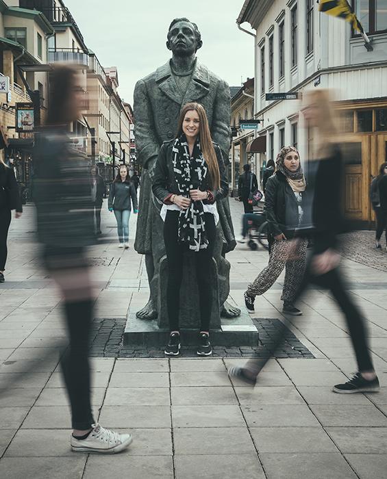 Ung kvinna står mitt bland folk som går omkring på stan.