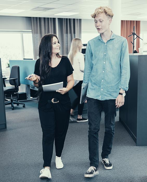 två unga människor på ett kontor, pratar med varandra