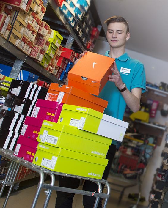 Ung man plockar iordning skokartonger på ett lager