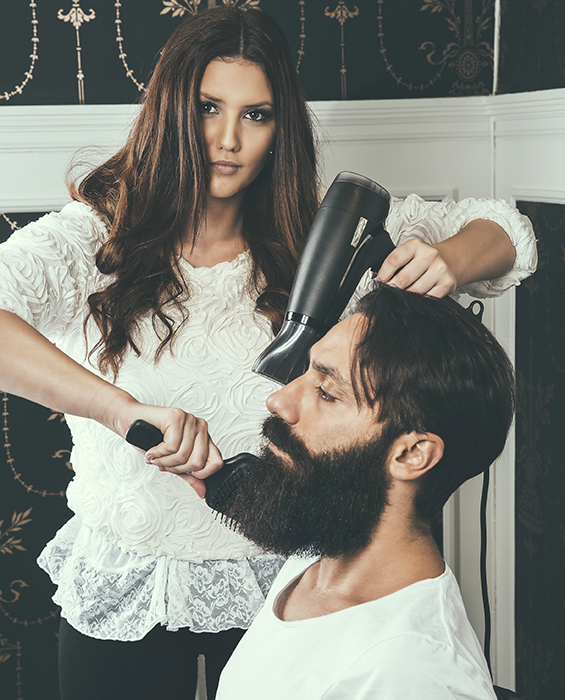 Ung frisör fönar en mans skägg.