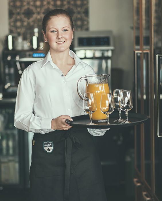 Ung servitris bär på bricka med glas och juice.