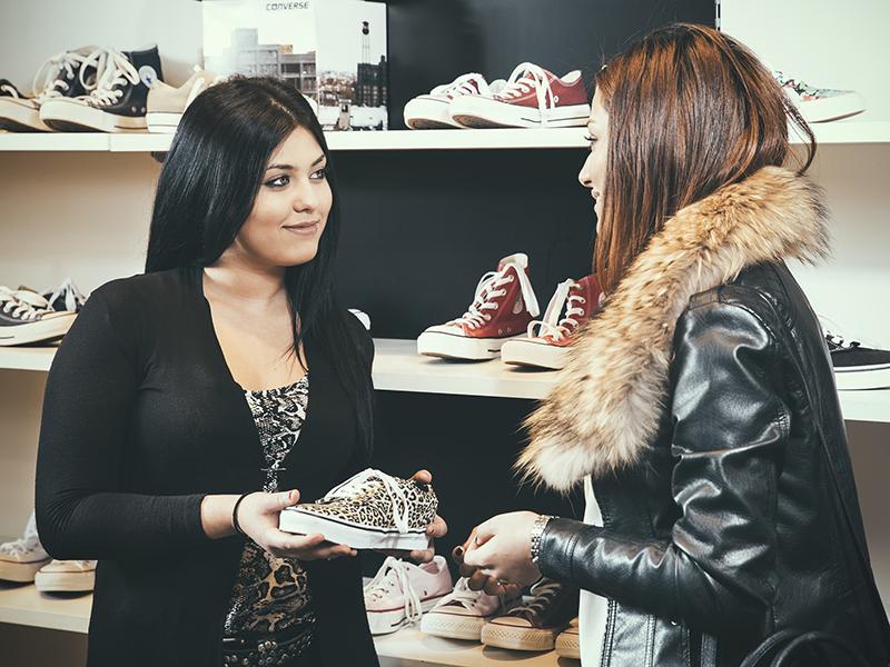 Ung kvinna hjälper kund i skoaffär.