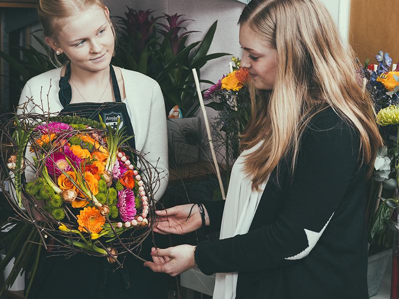 Ung florist visar kund en bukett