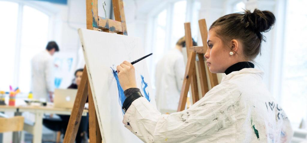 En tjej målar på en canvasduk.