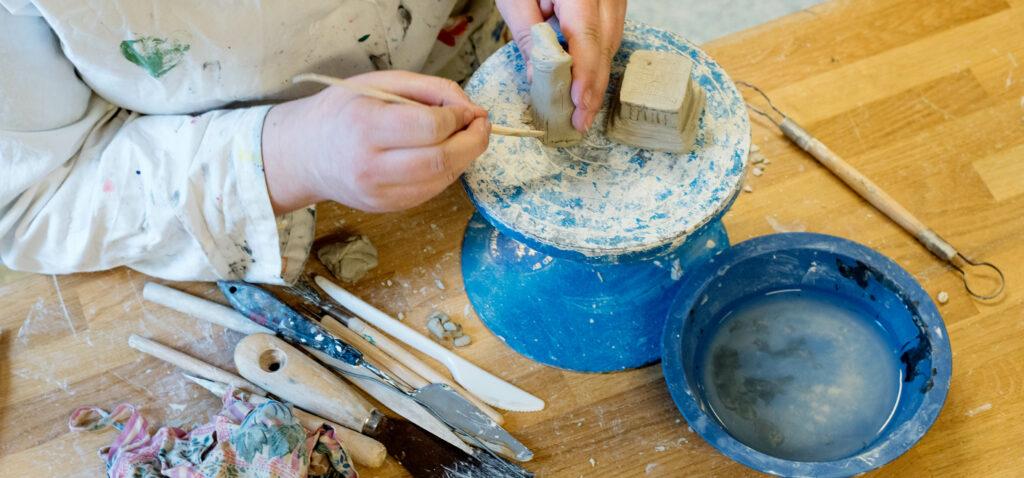 En elev skapar en form av lera.
