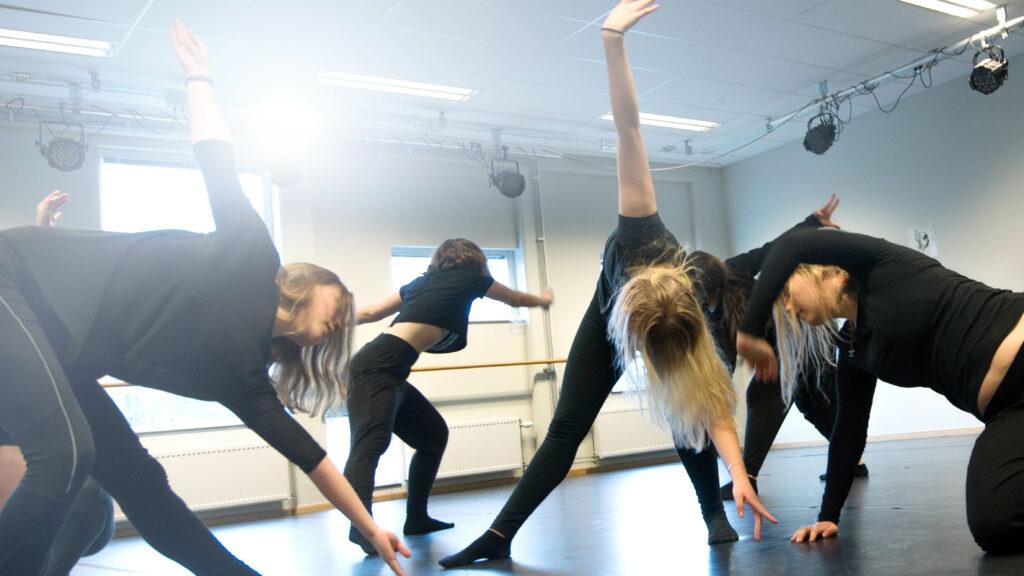 Bild på fem dansare mitt i en danslektion.