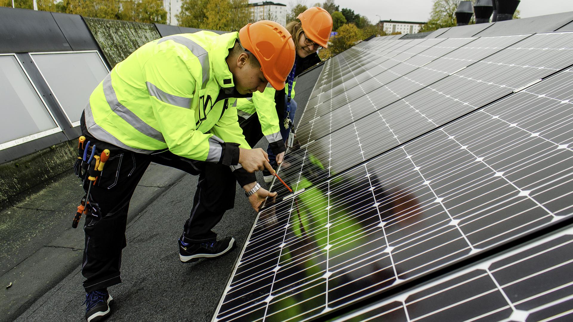 Elev och lärare installerar solpanel