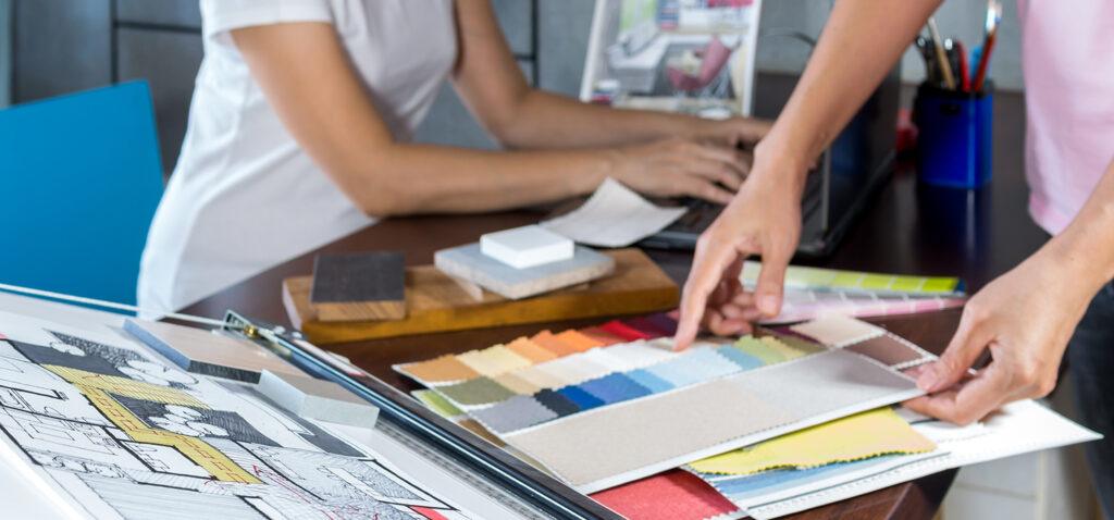 Kvinna skriver på dator och man väljer bland olika färg- och tygprover.