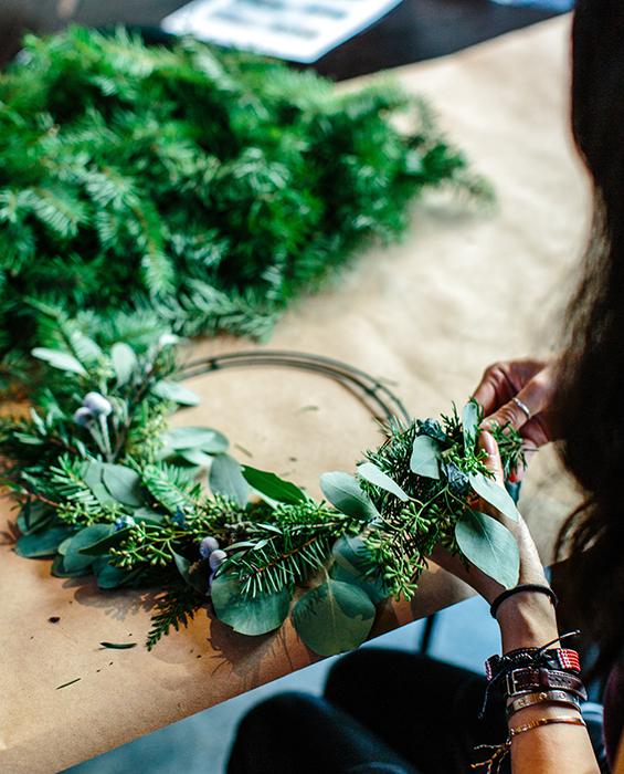 Kvinna binder krans av gröna blad.