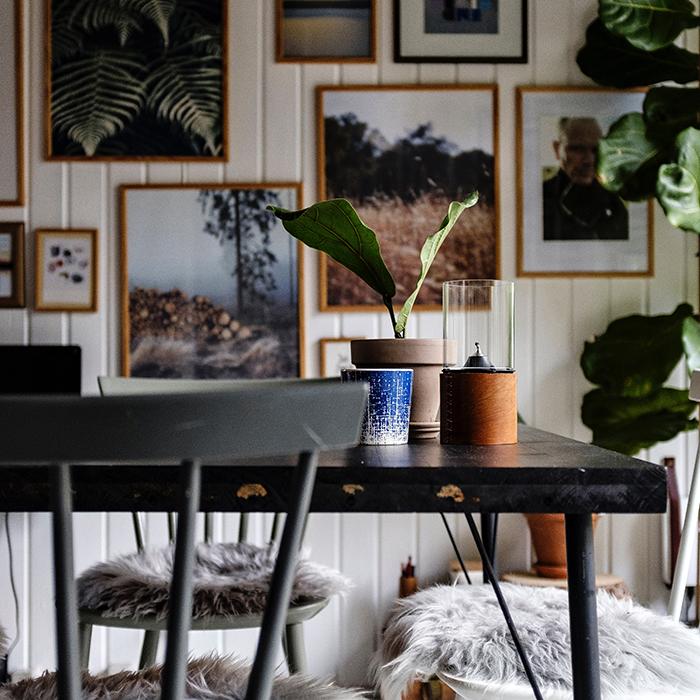 Tum med inredning av möbler, tavlor och växter.