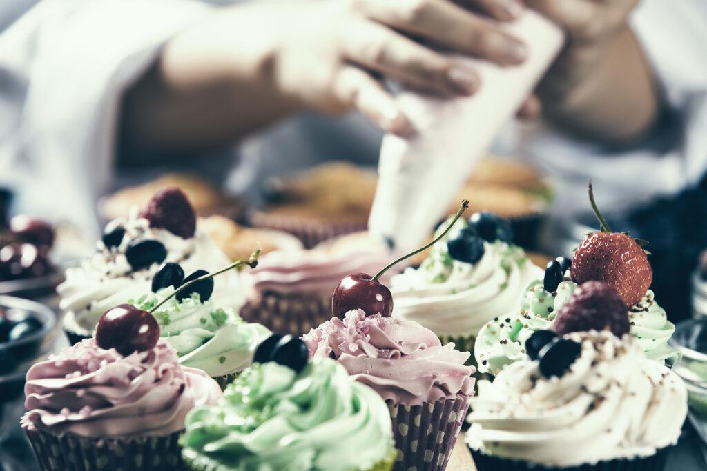 Konditor spritsar cupcakes.