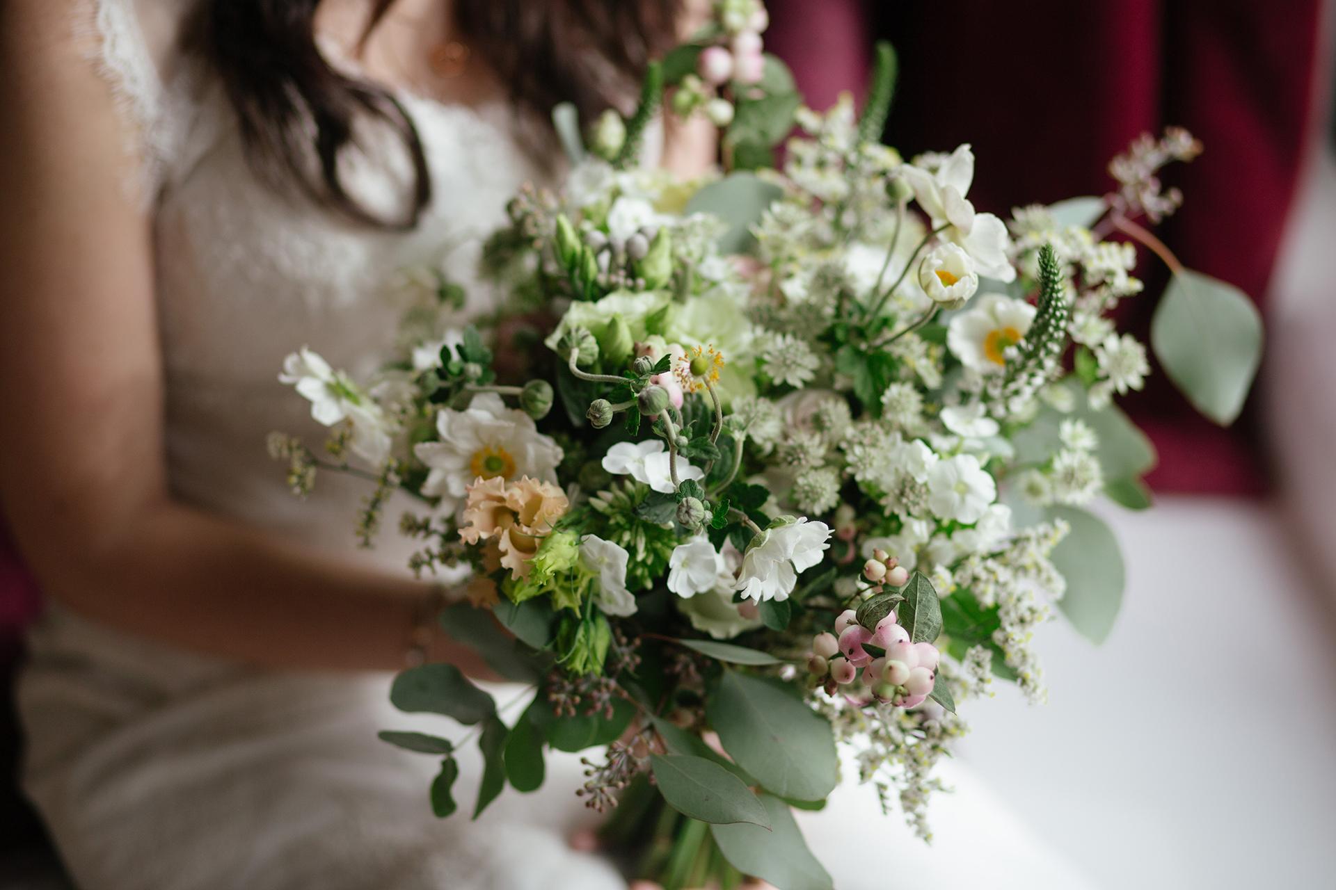Kvinna håller bukett med blommor.