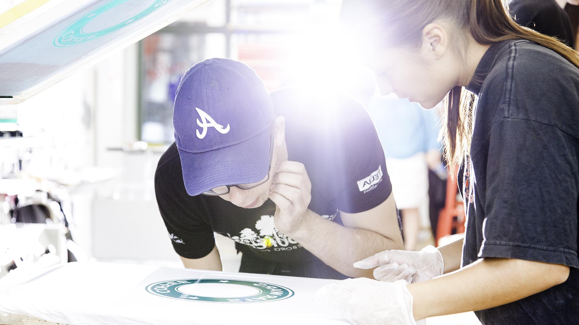 Två elever som trycker en tröja