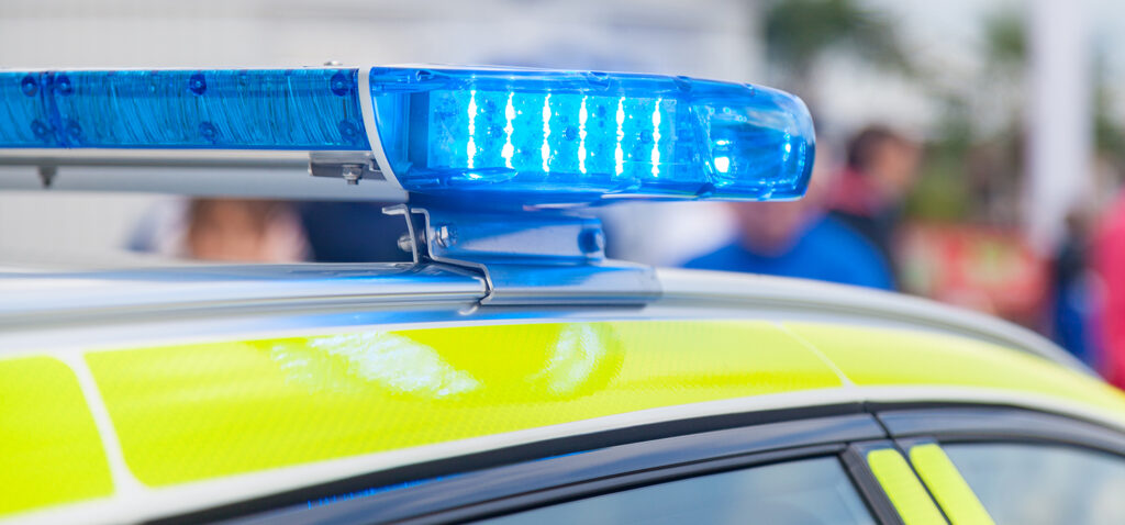 Taket på en polisbil med blåljuset tänt.