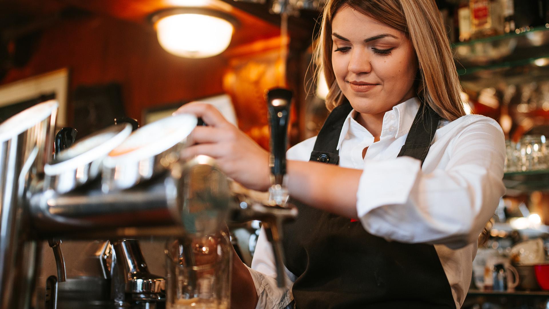 Un bartender häller upp öl.