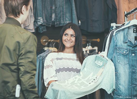 Ung kvinna visar t-shirt för kund i klädbutik.