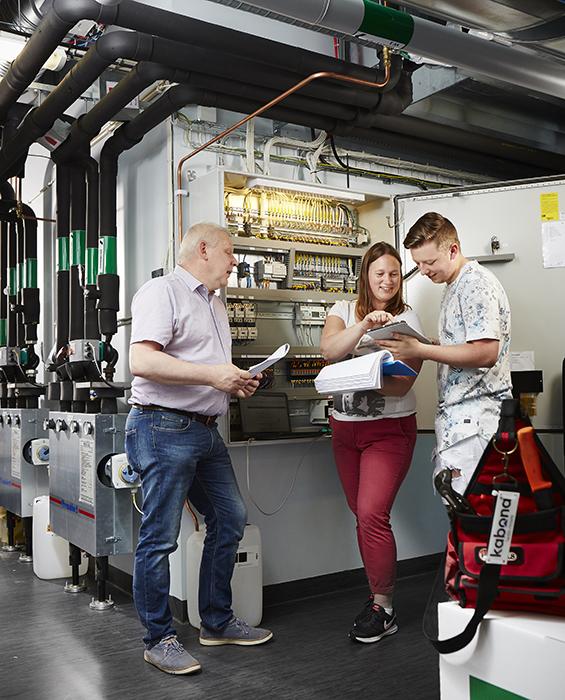 Äldre man instruerar elever vid ett elskåp på en arbetsplats.