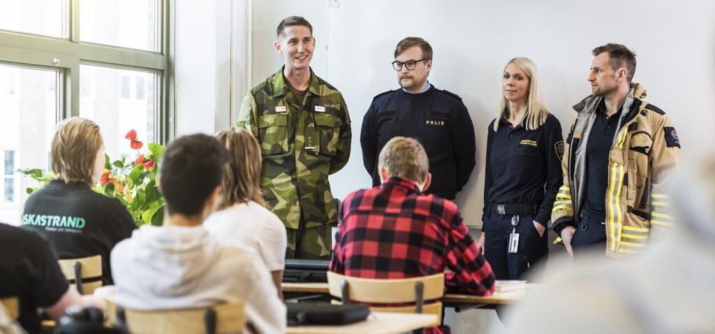 Uniformerade proffs presenterar sig för en klass elever
